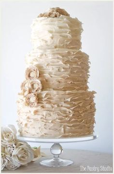 Ruffled spring #wedding #cake with pale pink fondant flowers & pearl embellishments.