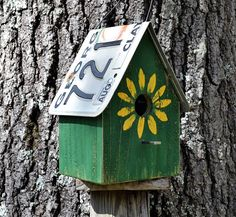 This rustic house is made from cedar and painted hunter green with a bright yellow sunflower and a flat rusty nail for a perch. The recycled license plate roof removes for easy cleanout. Has 1 1/4 hole for wrens and other songbirds. Comes with wire hanger. Measures 8 3/4 H X 6 1/2 W X 6 D.