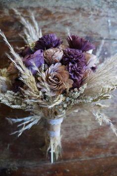 This beautiful sola flower bouquet is a charming and rustic addition to any wedding! After your wedding, simply place it in your favorite container for a lasting keepsake of your special day. 1/2 inch to 4 inch wide sola flowers are used, and this arrangement features: pampas grass,