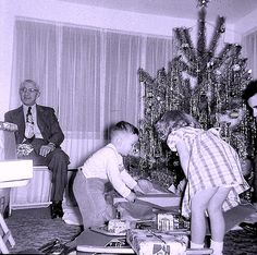 50's - look at all that tinsel on the tree. I remember back then that's what most of the tree decorations consisted of other than the lights.
