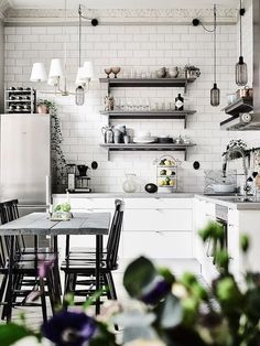 How To Make Your Kitchens Stylish & Unique To You | Kitchen lighting doesn't have to be boring spot/down lights.  Why not introduce a mix of styles like this gorgeous kitchen above which uses a traditional chandelier to define the dining area and contempo