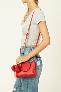 A structured faux leather mini crossbody featuring twin top handles, high-polish zip-top closure, a curb chain accent with twin pom poms, a removable adjustable shoulder strap, and one interior zip pocket.