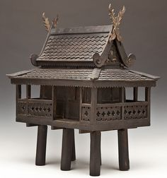 "Carved wood Southeast Asian spirit house, also known as san phra phum. With removable roof, enclosed porch, and six pillars on the bottom. MEASUREMENTS: 14"" x 19-1/2"""