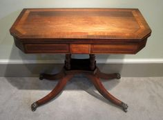Regency Rosewood and Satinwood Card Table-A very fine Regency period rosewood and satinwood swivel top card table, with double banded and strung decoration, on turned rosewood columns four splay base and original brass lion paw castors. Circa 1810.