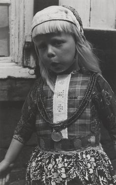 Jongen in Marker streekdracht. Hij is onder de vijf jaar en gekleed in rokkendracht. Hij is als jongen ondermeer herkenbaar aan de witte baan in zijn borstlap en zijn gebloemde schort. De jongen is gekleed in pinksterkleding, het zogenaamde 'Pinkster-bas'. 1943 #NoordHolland #Marken