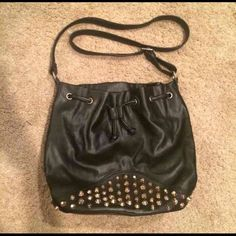 Black Studded Crossbody Bag This is an amazing black bucket style crossbody bag with gold studs along the front and sides. Very on-trend with a bit of an edgy or rocker vibe to it. The purse has an outside pocket on the back and a separate zippered compartment on the inside and side pockets. Has a drawstring and magnetic closure. Very clean and in great condition with no missing studs and was used less than three times. The only sign of wear is some scuffing along the actual drawstring on…