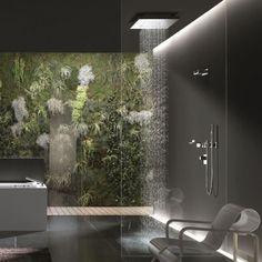 Un muro vivente piena di foglie, muschio e foglie di felce fornisce un punto focale naturale in questo bagno moderno.  Un apparecchio a pioggia è illuminato drammaticamente da sopra.