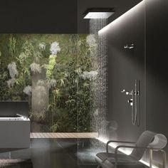 A living wall filled with foliage, moss and fern fronds provides a natural focal point in this modern bathroom. A rainshower fixture is lighted dramatically from above.