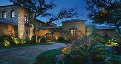 Use of accent lights to bring out details that make house/garden unique. Light at base of tree on left (tree accent), base of stone wall (accenting the different architecture vs stucco), bushes near house on left (mostly for shadows?), walls surrounding front door (helping guide people inside?). Clearly 2+ on ground in foreground planting (how did they choose those spots?), some sort of light in top right tree (what function does that serve?)