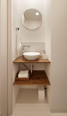 トイレ内の手洗いコーナー。手洗い付き便器ではお子さんの手が手洗いまで届きにくく、水はねの原因になっていました。そこでトイレを少し広げて手洗いスペースを設けました。カウンターは耐水塗装仕上げ。カウンター下はシンプルなオープン収納とし、丸い鏡とベッセル式(置き型)の手洗器でやわらかな印象にまとめました。床は淡いグレーの凹凸のあるCFシート張りとし、同じくグレーのモザイクタイルを水はねしやすい手洗器の前にあしらい、アクセントとしています。このわずかな壁の凹みによって機能的で広がりのあるトイレ空間となりました。 便器背面の吊戸棚は以前のものを再利用。手洗いカウンター上部には、手元が見やすいようにダウンライトを新設。メインのダウンライトと同時にON/OFFできます。洗面室は別にありますが、お子様はこの手洗いコーナーがお気に入り。お家に帰るとここで手を洗うのが日課になりました。 Bathroom Organisation, Washbasin Design, Laundry In Bathroom, 2 Bedroom House Design, Mirror Interior, House Tiles, Bathroom Design, Japan Interior, Muji Home