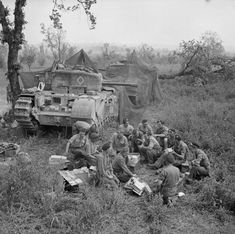 Churchill tank crews HQ Troop, 51st Royal Tank Regiment, 25th Tank Brigade, share out rations near their camouflaged vehicles before going into action in support of 1st Canadian Division, Italy.