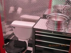 Polished diamond plate covers the first 4' feet of the walls and the vanity top- a  Craftsman roll around toolbox. The sink is a chrome whee...