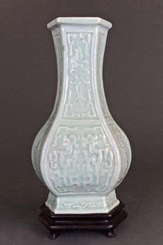 ANTIQUE CHINESE CELADON VASE ON WOOD STAND, Of hexagonal form, the sides molded with an interlocking pattern and a floral motif. On a short, slightly everted foot. Mark on the bottom.