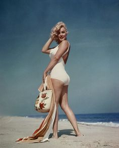 Marilyn Monroe on the beach in a white swimsuit. © Sam Shaw