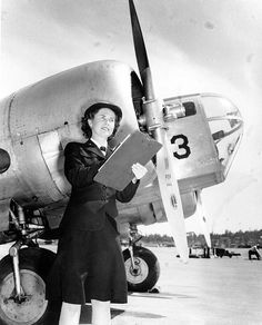 WAVES personnel Bernice Garrott marking off an aircraft check-off list, Naval Air Station, Seattle, Washington, United States, 7 Jul 1943; note SNB-1 training aircraft.