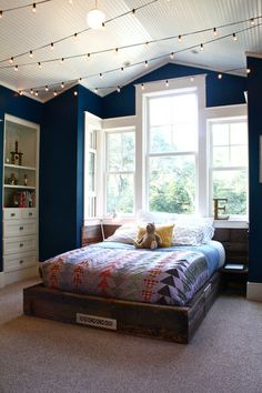dark blue walls trimmed in white, twinkle lights on the ceiling, recessed wall shelves/drawers, stunning picture window instead of headboard - I love this space!
