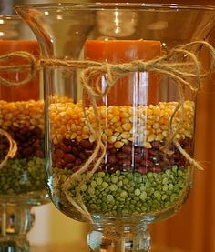 fall decorating with hurricane vases - popcorn kernels, red beans, and peas... Halloween - candy corn.....Chrstmas - cranberries, peppermint candys, red hots