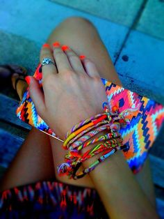 Brightly colored friendship bracelets, nails and clutch