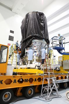Technicians Secure the Protective Covering Around CYGNUS. In the Space Station Processing Facility high bay at NASA's Kennedy Space Center in Florida the Orbital ATK CYGNUS pressurized cargo module is secured the KAMAG transporter and the crane has been removed.
