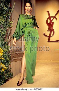 Yves Saint Laurent Autumn Winter Female wearing long satin green dress with thigh split - Stock Image