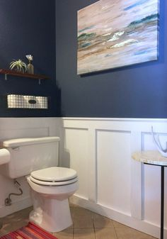 black flooring Crisp white DIY wainscoting and a striking, deep blue wall color elevate a formerly dull powder room. Find out how a few key projects and styling from Design Sponge make this a budget bath makeover. Wood Wainscoting, Dining Room Wainscoting, Bathroom Wainscotting, Wainscoting Height, Wainscoting Nursery, Blue Wall Colors, Floor Colors, Up House, Bath Remodel
