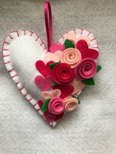 A Felt heart ornament perfect for Valentine's Day. The item pictured is ready to ship and the one pictured above is the item you will receive. Perfect to hang on a mantle (I'm in Florida and not many houses have them to perfectly photograph it), to hang on decorative reeds, an entry