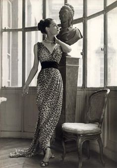 "Mitzah Bricard with sculpture, wearing a silk chiffon Christian Dior dress from the 1947 New Look Collection.  The first to recognize the leopard print as a reputable trend was Christian Dior. His iconic 1947 New Look collection ""featured two leopard dresses: the midi-length jungle sheath for day, and the silk chiffon Afrique gown for evening."
