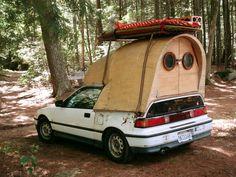 Tiny wood camper attached to a Honda Civic--Jay Nelson's Honda Civic camper. The fine woodwork shaping the arched living space provides a striking contrast to the vehicle below.