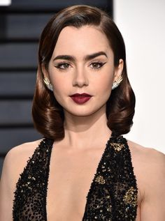 For a more polished look add a product with shine, then smooth and curl your hair into a look that exudes vintage Hollywood glam, like this look on Lily Collins. Image: Glamour