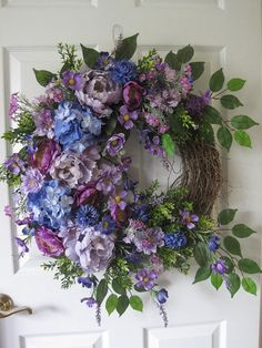 Spring Wreath, Summer Wreath, Four Season Wreath, Front Door Wreath, Home Décor, Garden Wreath, Grapevine Wreath, Handmade Wreath, Custom Wreath. Here we have a beautiful front door wreath, so pretty in shades of purple, featuring a grapevine wreath base filled with gorgeous purple peonies, hydrangeas, roses, buttercup, mums and wildflowers with mixed greenery, ferns and long wispy grasses. The finished measurements are 30 inches long by 30 inches wide by 6 inches deep, tip to tip. All of…
