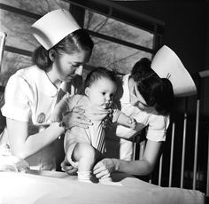 Two nurses help a baby to take a few steps at St Vincent's Hospital in Montclair, New Jersey, 1955.