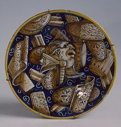 Plate with Trophies Italy, Castel Durante. 1546 Majolica; painting over opaque white tin glaze. Diam. 22 cm