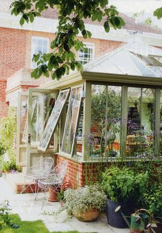 A simple conservatory with beautiful coloured paint that really makes it look like it's 'part of' the garden.