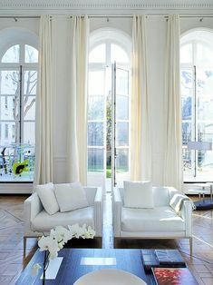 Here in the picture, you can see a white flower placed on the table along with books and besides that a white colored sofa is placed along with long white curtains. You can also try placing such thing to make your house look perfect, change the colors if you are not a fond of white color.
