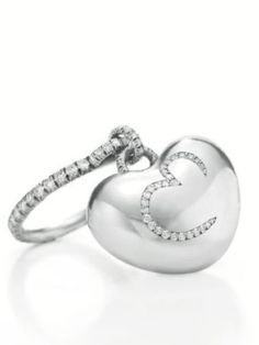 "A gift for Elizabeth Taylor from Mr Rosenthal on the occasion of her 70th birthday. A DIAMOND AND PLATINUM RING, BY JAR  Designed as an articulated platinum heart, set on one side with a single-cut diamond ""E"" and set on the other side with a single-cut diamond infinity sign, to the single-cut diamond hoop, mounted in platinum, ring size 5¾"