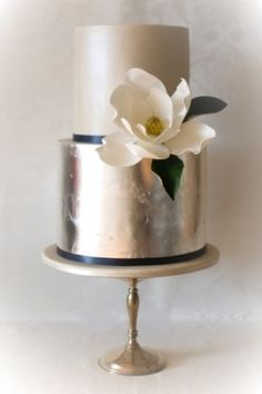 Metallic cake with navy ribbon and magnolia by Patricia Hardjopranoto of Yummy Cupcakes and Cakes We stock a wonderful selection of designer wedding dresses and run a closed door policy to provide you with the ultimate shopping experience. Metallic Cake, Metallic Wedding Cakes, Silver Cake, Gold Wedding, Cake Wedding, Metallic Gold, Gold Leaf, Pewter Wedding, Summer Wedding