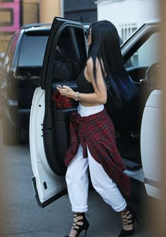 Kylie Jenner ••• Black crop top , white pants , flannel , black heels.
