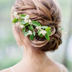 A relaxed low updo adorned with simple greenery is the perfect way to go classic with a boho touch. 🌿✨ #marthaweddings 📷: @brushfire_photo