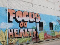 """... die Botschaft. """"Focus on Health"""" - Konzentriert euch auf Gesundheit - die Nachricht hätte man in den 1990er Jahren hier noch nicht lesen können. Die Wandgemälde dienen in diesen Zeiten auch eher nicht zum Abstecken des Reviers rivalisierender Straßeng"""