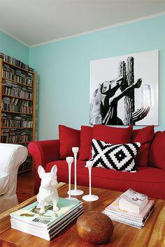 Salon avec sofa rouge, étagère de rangement pour CD, coussins noir et blanc et table en bois massif
