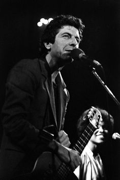 Leonard Cohen with Sharon Robinson in the background.  UPDATE: Photo by Pete Purnell from the October 30, 1980 concert at the Concertgebouw in Amsterdam.  Info kindly shared by Heck of a Guy who provides three other photos from this concert.