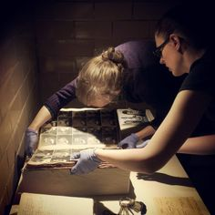 """ESP Archivist Erica Harman and Researcher Annie Anderson carefully set the mugshot book in place for """"Pop-Up Museum: Sin and Salvation."""" The exhibit opens this Saturday, April 12 and runs through April 22. Included with admission!"""