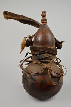 A Kwere medicine gourd from Tanzania. Here a calabash has been trained with a tight chord around its middle to take an hourglass shape so it can be suspended. The carved wooden stopper, depicting a mother with a baby on her back, identifies the gourd and its medicinal contents while acting as medium with the spirits that oversee the efficacy of the medicine. African Masks, African Art, Calabash Gourd, Water Flask, Painted Gourds, Hourglass Shape, Prop Design, Renaissance Clothing, Gourd Art