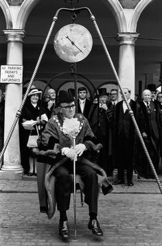 """Weighing-in ceremony in High Wycombe, Buckinghamshire, May 1974.   The newly elected mayor, Victor Lay, is seen here being publicly weighed. """"It was all about making sure you got good value for money when you elected the mayor,"""" says Sykes. """"If he put on weight over the ensuing year, then it was deemed he was living off the fat of the land — i.e., off your taxes."""" The crowd would cheer or boo loudly, depending on the result."""