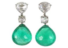 Platinum earrings featuring 22.4-carat emerald drops of antique Colombian emeralds in a briolette cut. The top diamond stud is antique fancy...