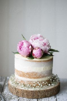 Naked wedding cake decorated with fresh flowers by Ruth Black for Stocksy United