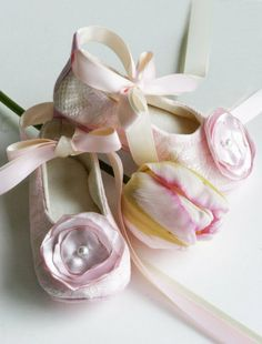 """The height of elegance, this off-white lace ballet slipper is perfect for the little flower girl. And, just as easily, they can dress up a pair of jeans. Pink lace upper is lined with a off-white colored satin and topped with handmade cloth flowers, each with a pearl button center, giving these shoes a very """"adult"""" aesthetic. This ballet slipper can be worn traditionally, with the off-white satin ribbon at the ankle, or is easily removed for an updated fashion flat look #timelesstreasure"""