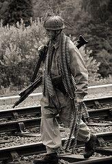 A German paratrooper carrying a machine gun & extra ammo belts.