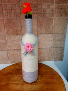 Garrafa decorada com la branca e cinza Acabamento com tranca de la e flor de feltro