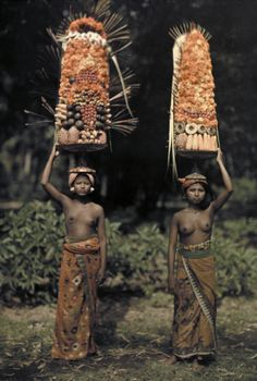 Two Balinese women carry temple offerings of fruit on their head.